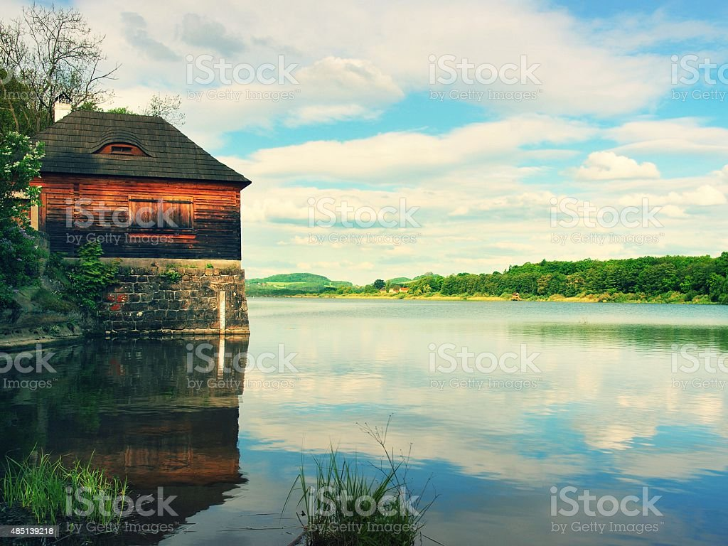 Morning lake with old style wooden fishing hut on bank stock photo