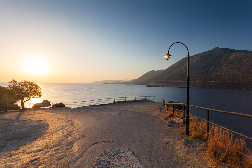 Morning landscape with lamp near viewpoint, mountains and sea.