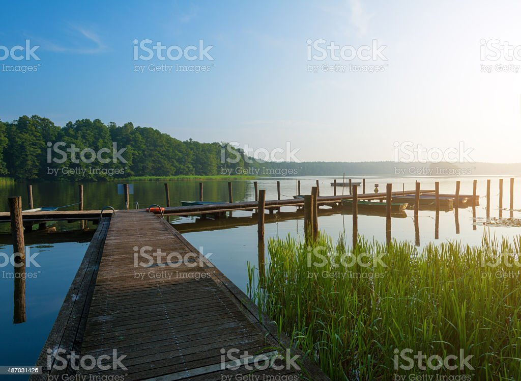 Morning light at a lake in Mecklenburg with landing stage stock photo