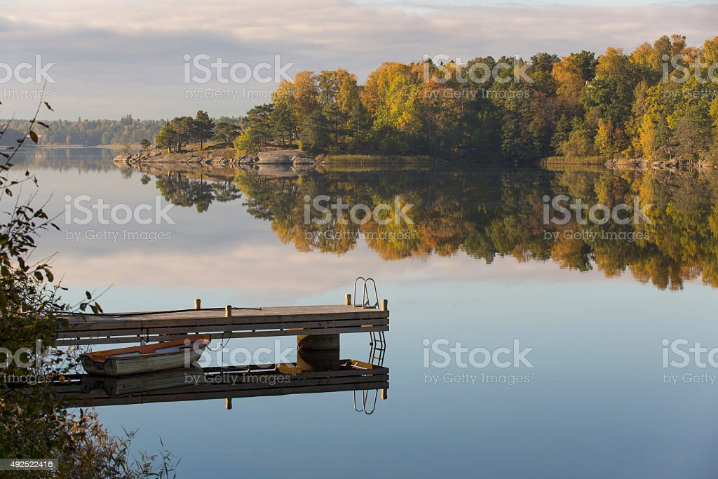 Morning light at the lake boat and jetty landscape stock photo
