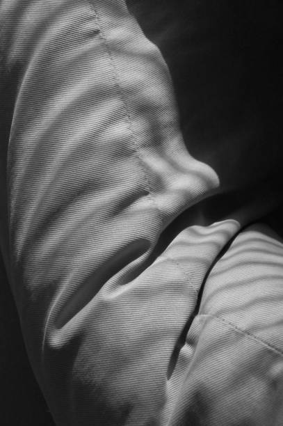Morning light drops shades in black and white on a pillow in a living room Shades of blinds on a pillow in a living room in black and white on an early morning in february werken stock pictures, royalty-free photos & images