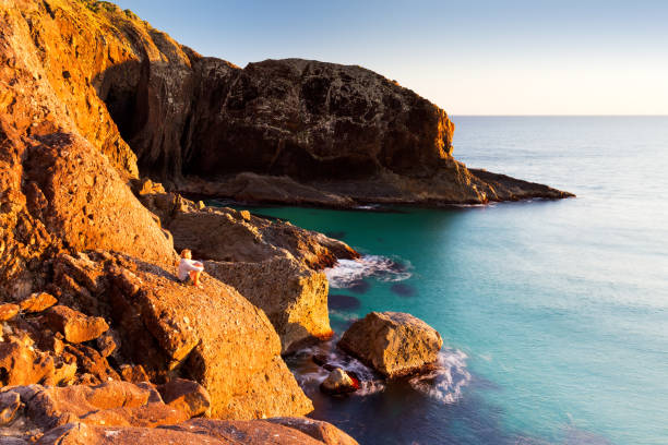 Morning Light Illuminates an Onlooker and a Rugged Australian Coastline stock photo