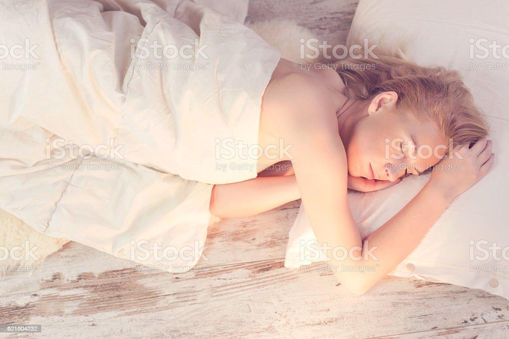 morning light illuminates woman sleeping in bed foto stock royalty-free