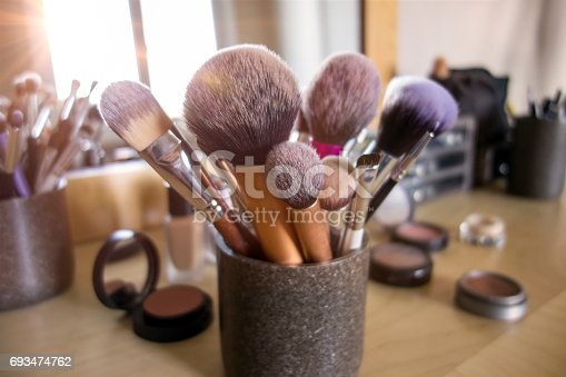 make up brushes on a wooden nightstand with sunlight