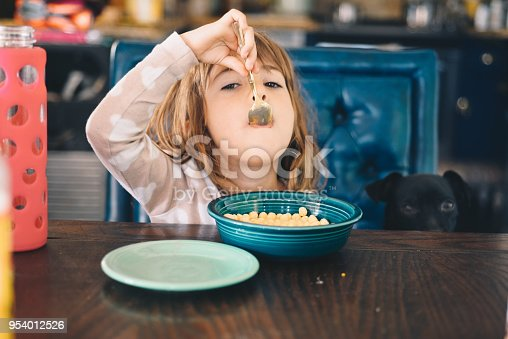 Adorable little girl, 4 year old brunette, sits at the kitchen table in a domestic home eating a bowl of cereal. She has on pajamas and has bed head with messy hair, candid domestic