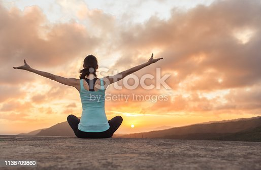 Woman meditating outdoors in the morning.