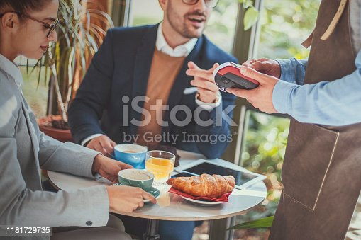 Two young business people having a breakfast meeting in a coffeeshop. A waiter in a leather apron is processing their credit card payment.