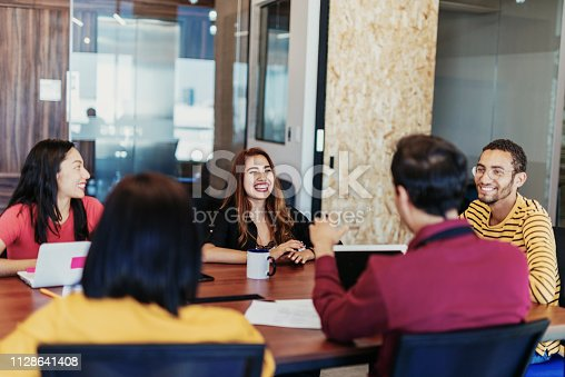 istock Morning meeting with colleagues - Latin millennials working on mobile app development 1128641408