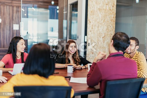 istock Morning meeting with colleagues - Latin millennials working on mobile app development 1128641469