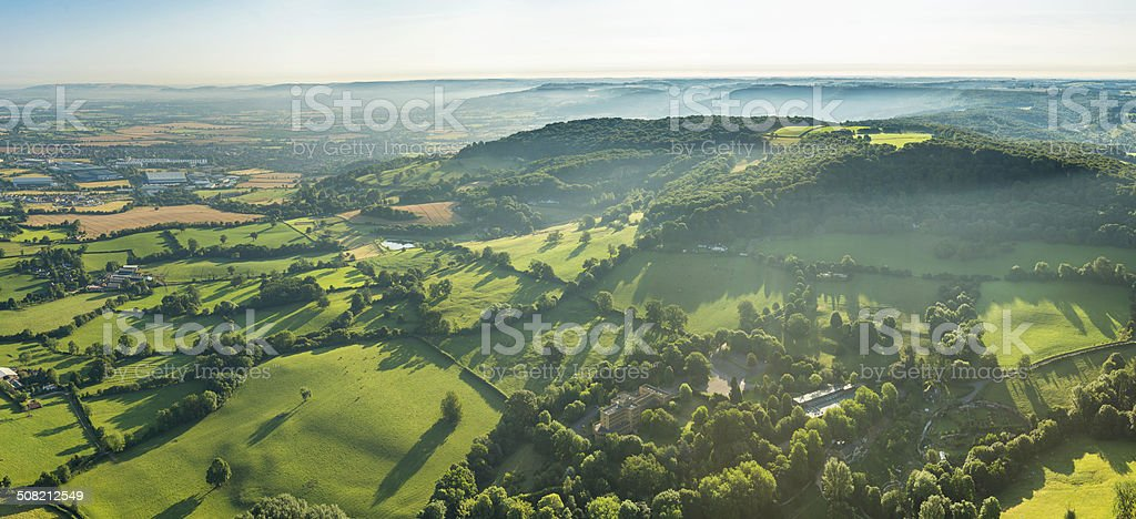 Morning mist swirling through vibrant green summer landscape aerial panorama stock photo