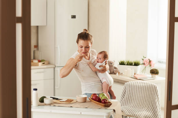 Morning of busy mother who is eating porridge for breakfast in kitchen while rocking her baby stock photo