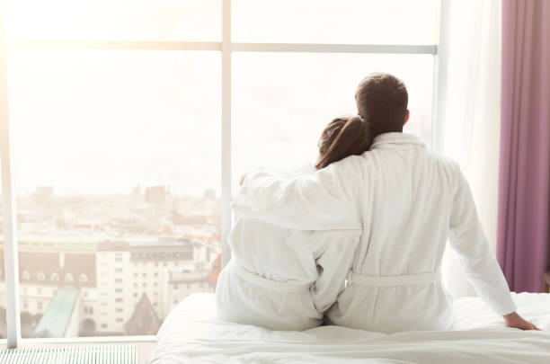 morning of happy young couple resting in hotel room - accappatoio foto e immagini stock