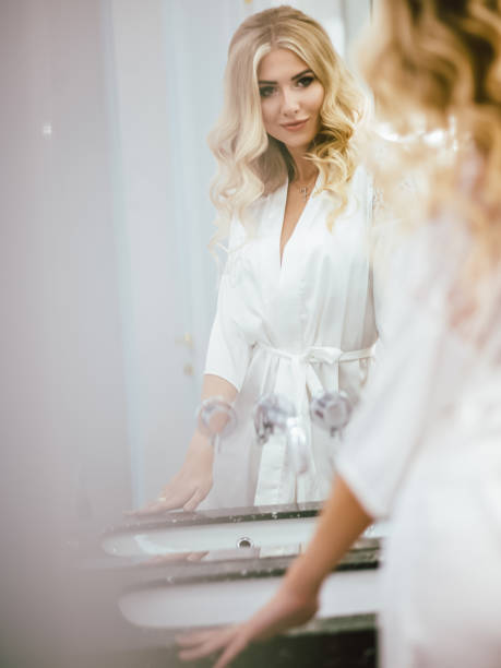 Morning of the bride, young girl admires herself in the mirror young girl in a white peignoir admires herself in the bathroom mirror near the sink fresh start morning stock pictures, royalty-free photos & images