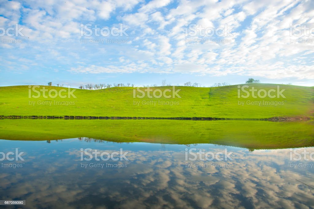 Morning on the lake with green hills and reflection stock photo