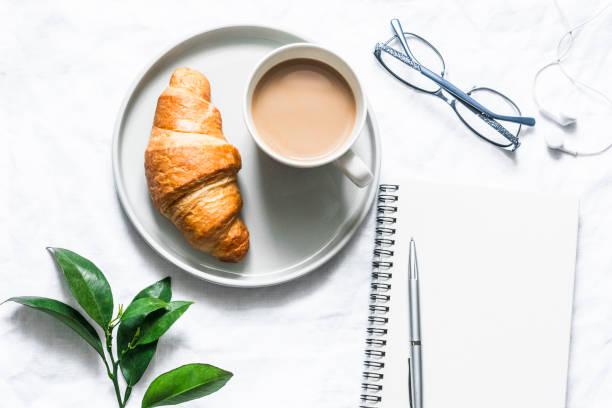 Morgens Plan. Kaffee, Croissant und ein sauberes leeres Notebook auf hellem Hintergrund, Top-Ansicht. Flache Laien, Kopierplatz – Foto