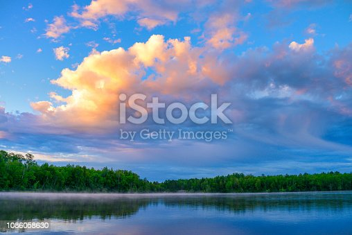 Puffy clouds morning tree reflection in lake