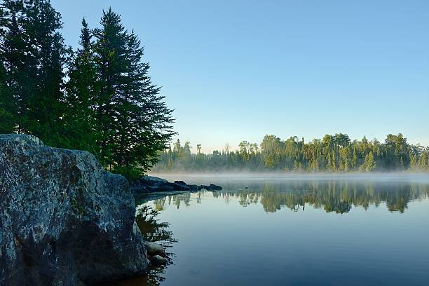 Morning Reflections on a Foggy Wilderness Lake Morning Reflections of a Forest on a Foggy Wilderness Lake minnesota stock pictures, royalty-free photos & images