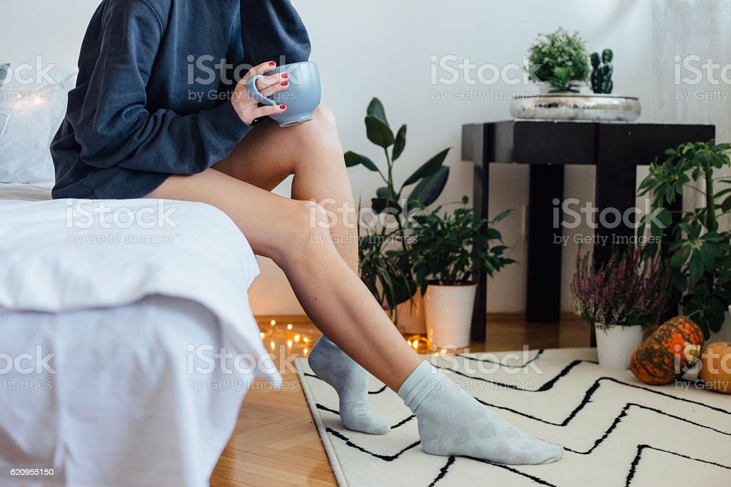 Morning relaxation Happy young woman with cup of coffee or tea in bed at home bedroom, she enjoy in weekend and morning in bad. Adult Stock Photo