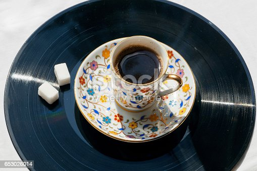 istock Morning relaxation with old style music concept. Record vinyl and cup of coffee on it. 653026014