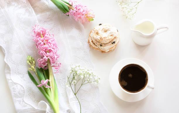 romantik frühstück, tasse kaffee, milchkännchen und kuchen mit dekor von rosa hyazinthe. frühling-konzept. ansicht von oben. - spitzenkekse stock-fotos und bilder