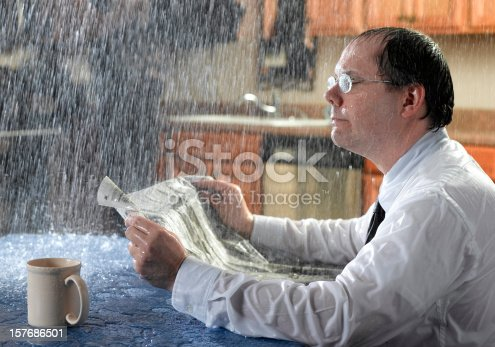 A man reads the paper as a bad roof leak allows rain down on him.