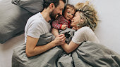 Photo of young parents enjoying morning routine in a cosy bed with their baby boy