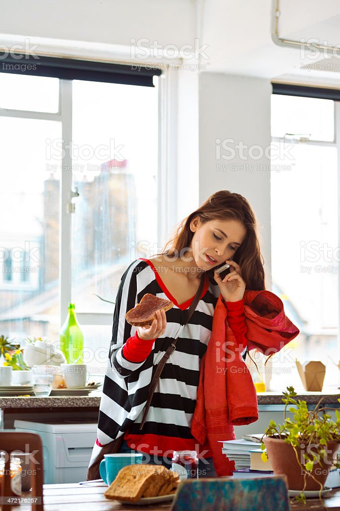 Morning rush Young woman going out. Standing in the kitchen talking on phone and eating breakfast in hurry. 20-24 Years Stock Photo