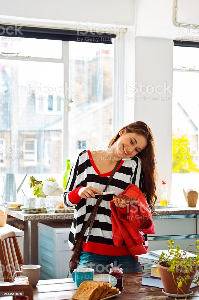 Morning rush Cheerful young woman going out, standing in a kitchen at home, making a sandwich and talking on phone. 20-24 Years Stock Photo