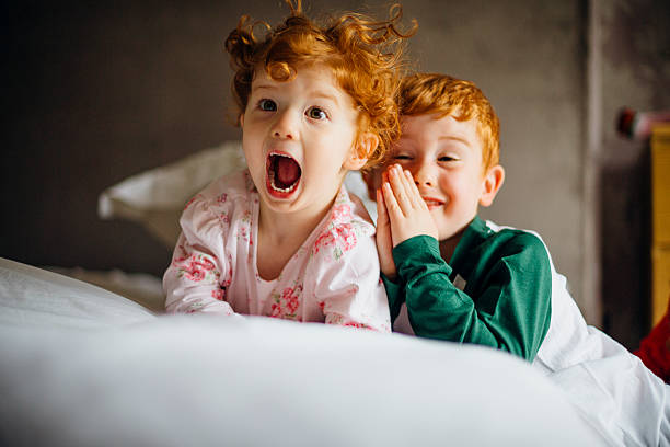 Morning Silliness Little girl and her older brother are being silly for the camera in the morning. They are in their pyjamas in their mother's bed. brother stock pictures, royalty-free photos & images