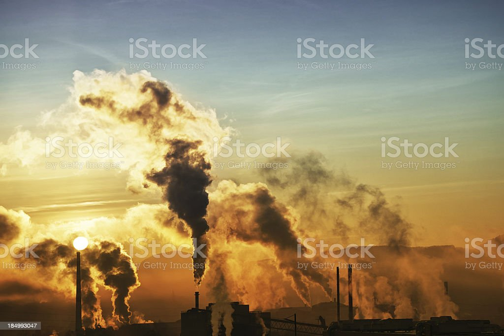 Morning smoke from factories with rising sun - wide stock photo