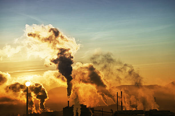 morning smoke from factories with rising sun - wide - air pollution stock pictures, royalty-free photos & images