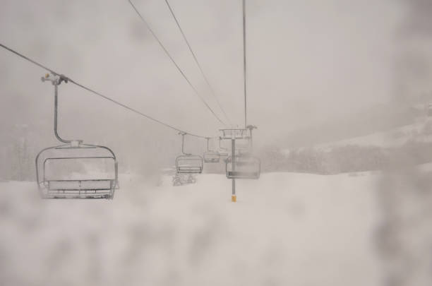 Morning snow falling over the mountain on Ski lift stock photo