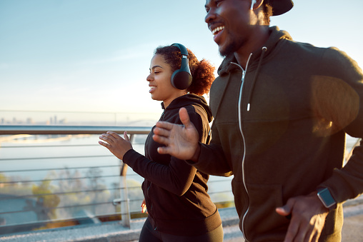 Morning sport. Young smiling african couple in headphones jogging together on the bridge. Happy African man and woman enjoying running outdoors. Side view. Sport. Running. Healthy lifestyle