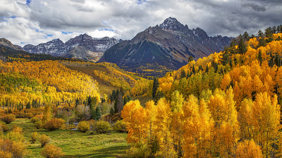 Morning Sun Shining on Autumn Foliage with San Juan Mountains in the Background on a cloudy day