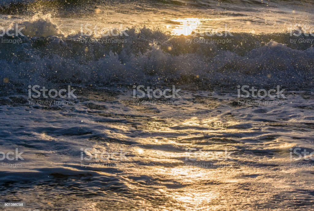 morning sunlight shigning through seaspray and water splashes as ocean waves break near the shore stock photo