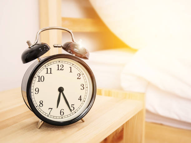 morning time background, retro alarm clock near the bed at home. - alarm clock stock photos and pictures