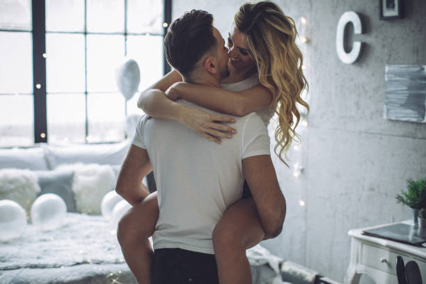 Morning Valentine's romance Couple on Valentine day enjoy in love. They are in bedroom and having romantic moment together romance stock pictures, royalty-free photos & images