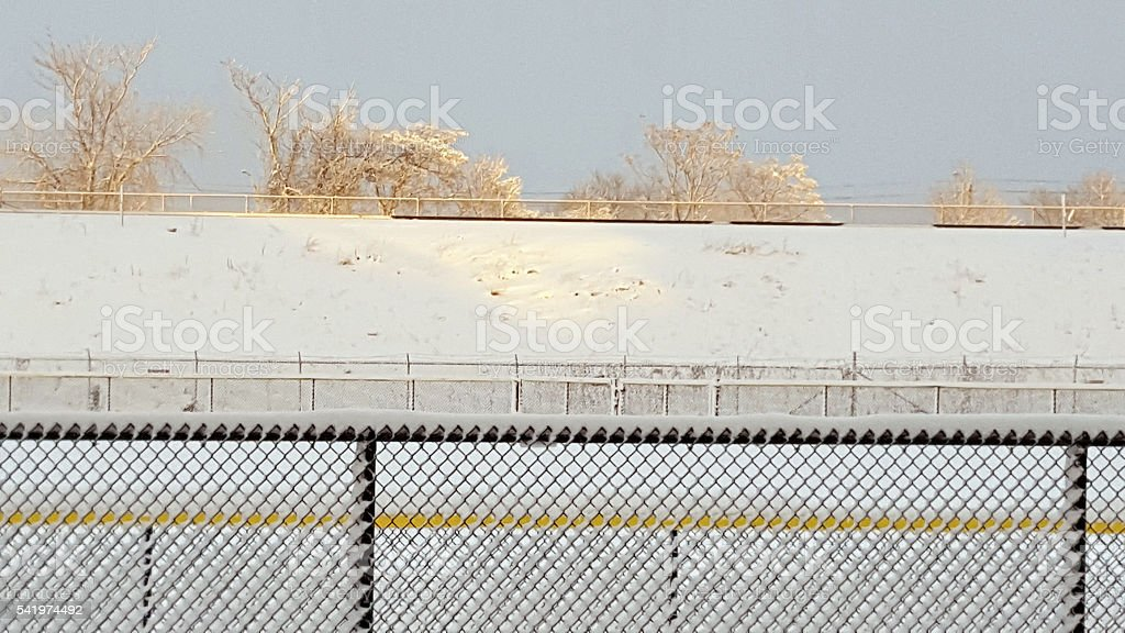morning view railway tracks in snow with trees brown fence stock photo