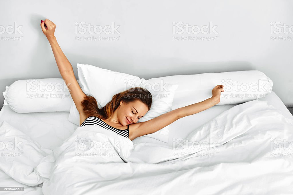 Morning Wake Up. Woman Waking Stretching In Bed. Healthy Lifestyle stock photo