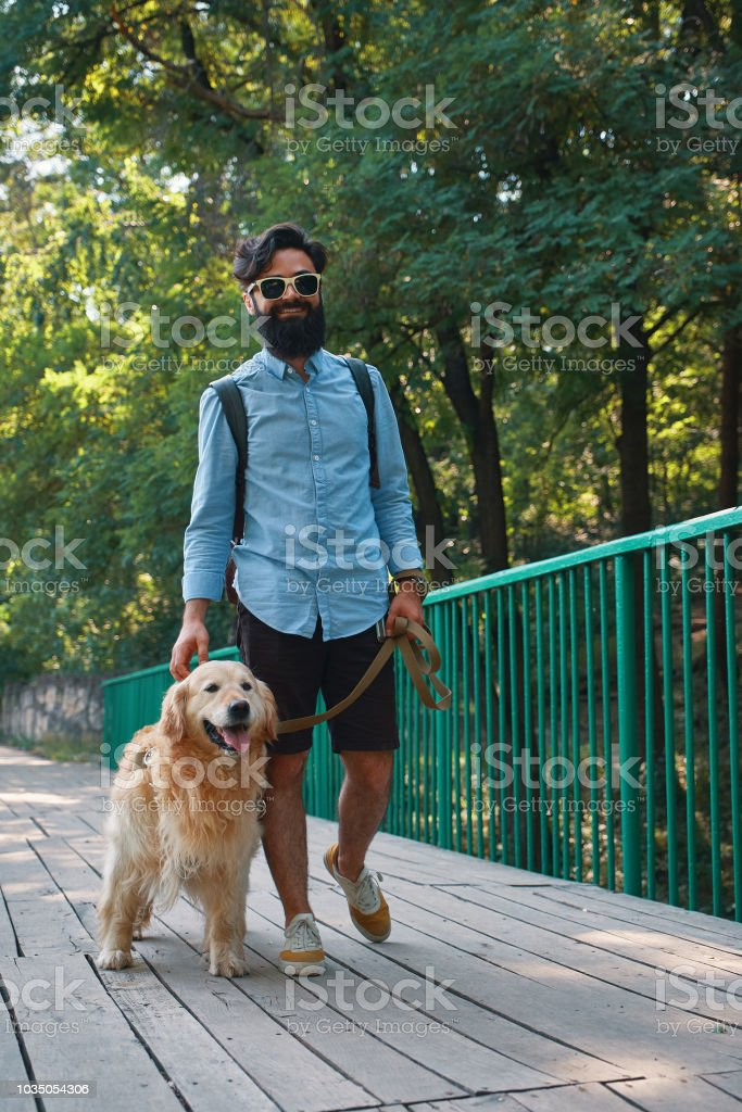 Morning walk with dog. Young man with his labrador retriever on the...
