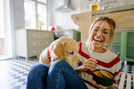 Photo of young woman and her dog in a kitchen at the morning