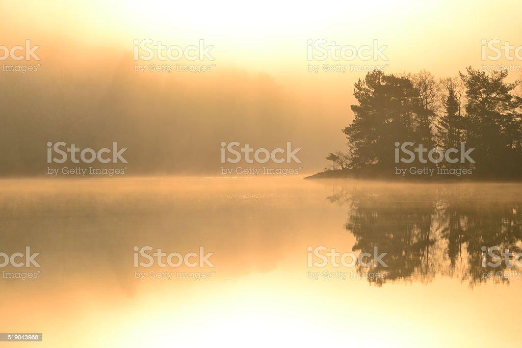 Morninghaze on lake with an island, lika a mirror stock photo