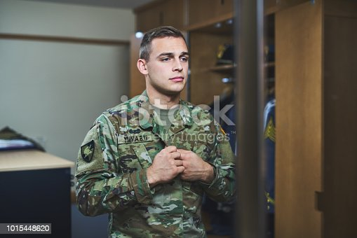 Shot of a young soldier standing getting dressed in the dorms of a military academy