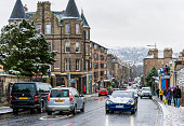 Edinburgh, Scotland - A Tesla and other cars on the road, and pedestrians on the pavement during snowy weather in the Scottish capital.