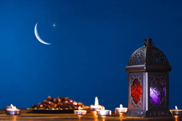 moroccan, arabic lantern and dates on on an old wooden table with the night sky and the crescent moon and the star behind. greeting card for muslim community holy month ramadan kareem. free space - eid stock pictures, royalty-free photos & images