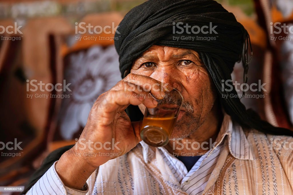 Moroccan man drinking Maghrebi mint tea. stock photo
