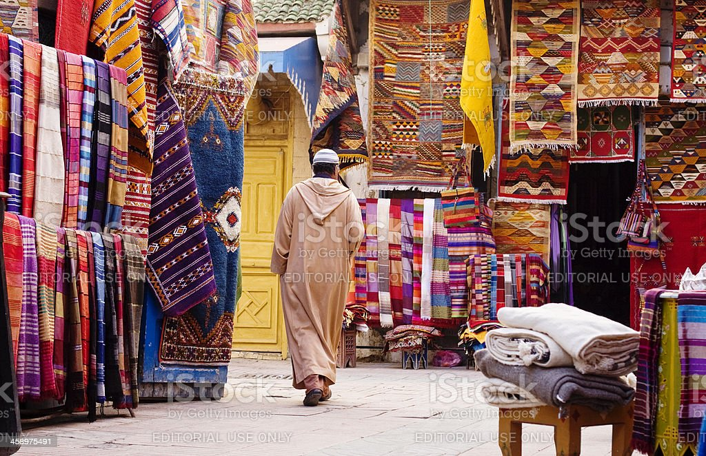 Moroccan man passing by the carpet sellers, Morocco stock photo