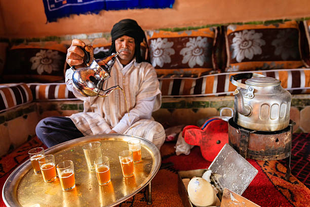 Moroccan man preparing Maghrebi mint tea. Maghrebi mint tea is a green tea with mint leaves. Tea occupies a very important place in Moroccan culture and is considered an art form.http://bem.2be.pl/IS/morocco_380.jpg mint leaf culinary stock pictures, royalty-free photos & images