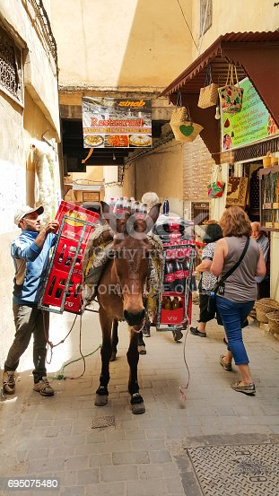 istock Moroccan Man Unloading Coke from a Mule 695075480