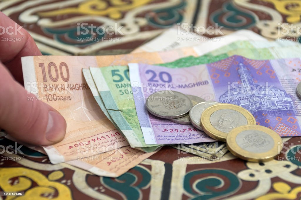 Moroccan Money - Dirham Coins and Notes with a hand stock photo
